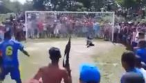 Brazilian footballer takes penalty kick in front of machine gun-toting fan